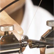 Brunissoir utilisé pour polir les pivots des axes sur un tour d'horloger actionné à la main à l'aide d'un archet.